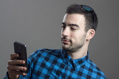 Close up moody portrait of young casual man typing text message on mobile phone. Over gray studio background Royalty Free Stock Images
