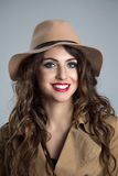 Close up moody portrait of young woman wearing hat and beige coat smiling Royalty Free Stock Image