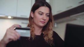 Close-up Mooi online vrouwen` s bankwezen met een creditcard bij de lijst stock video
