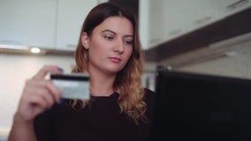 Close-up Mooi online vrouwen` s bankwezen met een creditcard bij de lijst met een goede stemming stock video