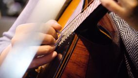 Close-up mooie akoestische gitaar die door vrouwenzitting worden geminimaliseerd, musicusconcept Vrouw die de gitaarclose-up spel royalty-vrije stock afbeeldingen