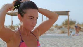 Close-up Mooie Gelooide Vrouw die Haar Haar verzamelen die samen, op het Strand zitten stock footage