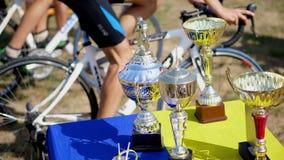 Close-up, mooie gouden en zilveren koppen, toekenning op de achtergrond van fietsen, hometrainers sportief benenpedaal  stock videobeelden