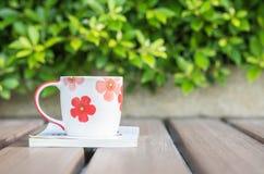 Close-up mooie kop van koffie op wit boek op vage houten lijst en groene installatie op de tuin geweven achtergrond, relaxati Stock Afbeeldingen
