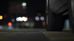 Close-up mooie slanke vrouwelijke benen in blauwe hoge hielschoenen die in auto bij nacht over citylights bokeh achtergrond krijg stock footage