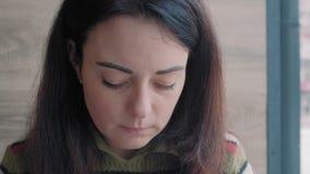 Close-up, Mooie Vrouw die Roomcakes eten en uit de Vensterzitting in een Koffie kijken stock videobeelden