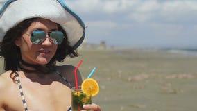 Close-up mooie vrouw die zonnebril en hoed dragen, die lange drank op strand hebben stock videobeelden