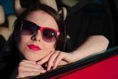 Close-up mooie vrouwelijke tiener met rode zonnebril in rode auto Stock Afbeeldingen