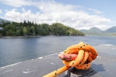 Close-up of a mooring rope with a knotted end tied around a cleat on a ferry. stock images