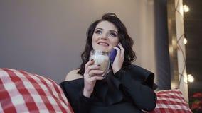 Close-up Morena bonita da mulher gravida em um bodysuit apertado preto com um colar que beba o chocolate morno com leite filme