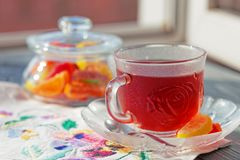 Close up of a morning black tea and colorful marmalades in glass jar on wooden table royalty free stock photo