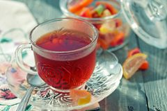 Close up of a morning black tea and colorful marmalades in glass jar on wooden table royalty free stock photos