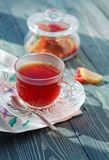 Close up of a morning black tea and colorful marmalades in glass jar on wooden table royalty free stock images