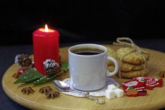 Close up of morning holiday breakfast. Homemade Christmas cookies, coffee and burning candles on wooden table. Stock Photo