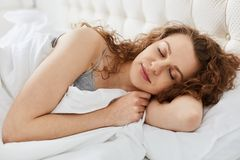 Close up morning portrait of attractive young sensual woman laying on white bed close her eyes, female has long curly hair and stock image