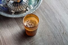 Moroccan traditional Tea table. Close up of a moroccan glass of tea on a wooden table Royalty Free Stock Photos