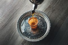 Moroccan traditional Tea table. Close up of moroccan traditional tea pot and glass on a silver plate Royalty Free Stock Image