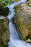 Close up of mossy rock with blurred flowing water rushing downstream Royalty Free Stock Image