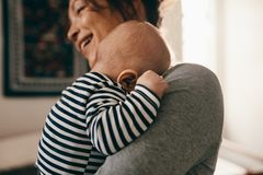 Close up of a mother carrying her sleeping baby royalty free stock photo