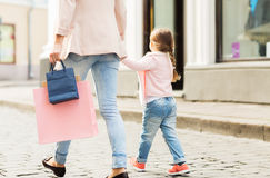 Close up of mother and child shopping in city. Sale, consumerism and people concept - close up of mother and child with shopping bags walking along city street royalty free stock photos