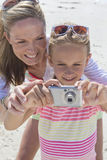 Close up of mother and daughter with digital camera on sunny beach Royalty Free Stock Photos