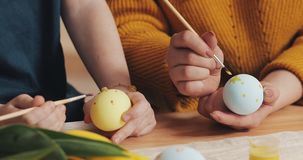 Close up of mother and daughter hands coloring easter eggs with colors and brush. Colorful easter eggs. Preparation of