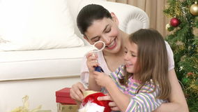 Close up of mother and daughter having fun with Christmas presents stock video footage