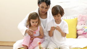 Close up of mother, daughter and son playing toy cubes on the bed Royalty Free Stock Images