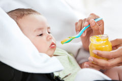 Close-up of a mother giving food to her cute baby Stock Photos