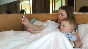 Close-up of a mother with a little son takes a selfie on the phone lying on bed. Close-up of a mother with a little son takes a selfie on the phone lying on the stock video