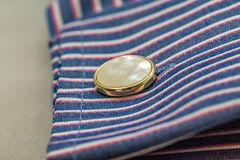Close up of mother of pearl cufflink and work shirt. Close up of mother of pearl cufflink in a double cuffed stripy work shirt stock images