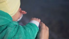 Mother with small baby in her hands stay on beach. Close-up. Mother with small baby in her hands stay on beach, back view. She shows him the sea and gently holds stock footage