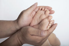 Close up of mothers hands holding the feet of her son, studio shot Stock Image