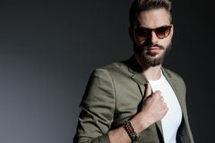 Close up of motivated man adjusting his green jacket`s collar. And looking to the camera while wearing sunglasses and a white t-shirt, standing on gray studio stock photography