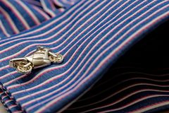 Close up of motorbike design cufflink and fashionable stripy work shirt. Close up of motorbike design cufflink in a stripy double cuffed work shirt royalty free stock photography