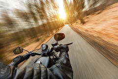 Close-up of motorbiker riding on empty road. In forest with sunrise light, concept of speed and travel in nature Stock Photography