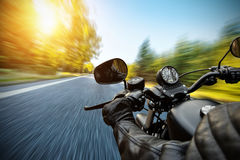 Close-up of motorbiker riding on empty road. In forest with sunrise light, concept of speed and travel in nature Royalty Free Stock Photography