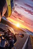 Close-up of motorcycle driver riding in Alpine highway. stock photography