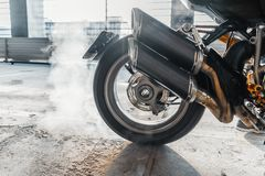 Close up of motorcycle wheel burnout at parking. stock photography