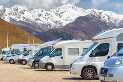 Close up motorhomes parked in a row on background snow mountain nature landscape royalty free stock photos