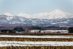 Close up Mount Yotei inactive stratovolcano with village on the foot hill and snow cover on the ground in winter in Hokkaido Stock Images