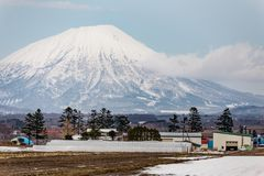 Close up Mount Yotei inactive stratovolcano with village on the foot hill and snow cover on the ground in winter in Hokkaido Stock Photo