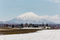 Close up Mount Yotei inactive stratovolcano with village and snow cover on the ground in winter in Hokkaido, Japan Stock Photos