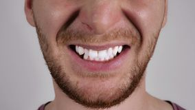 Close up mouth of an irritated person. Part of face caucasian man. Unrecognizable male with beard anger. Person showing grin stock photos