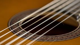 Close-up of the strings of a classical acoustic guitar. Close-up of the mouth and strings of a classical acoustic guitar.n Royalty Free Stock Images