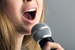 Close-up of a mouth of a woman singing into a microphone. Close-up of a mouth of a young woman singing into a microphone a song with emotions on a gray stock photos