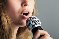 Close-up of a mouth of a woman singing into a microphone. Close-up of a mouth of a young woman singing into a microphone a song with emotions on a gray Stock Photography