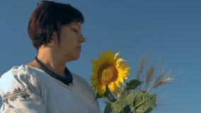 Close-up, movimento lento, mulher bonita da roupa no olhar nacional pensativamente em um ramalhete de brotos do trigo e girassol video estoque