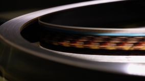 Close up of a moving 35mm film stripe in a movie theater
