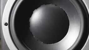 Close up of moving professional sub-woofer on recording studio. A black round audio speaker pulsating and vibrating from